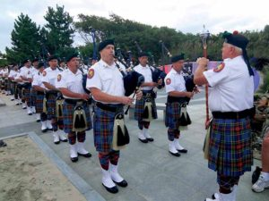Bagpipers play a solemn hymn.