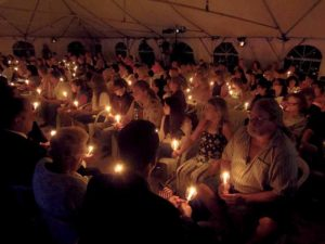 Attendees light and  hold memorial candles.